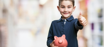 boy smiling with piggy bank
